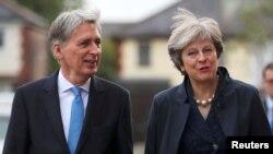 برطانیہ کی وزیرِ خارجہ تھریسا مے اور وزیرِ خزانہ فلپ ہیمنڈ حکمران جماعت کے ایک اجلاس میں شرکت کے لیے آ رہے ہیں۔ (فائل فوٹو)