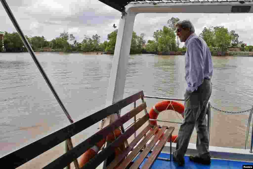 U.S. Secretary of State John Kerry rides a boat through the Mekong River Delta, Dec. 15, 2013.
