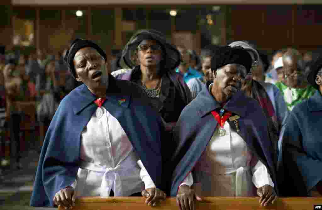 Women sing during a mass commemorating the late South African former President Nelson Mandela in Soweto, near Johannesburg.