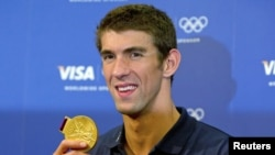 FILE - Michael Phelps poses with his gold medal for the 4x100m medley relay during a news conference with his sponsors at the London 2012 Olympic Games, August 5, 2012.