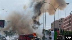 Khói bụi của vụ nổ thứ hai khi nhân viên cứu hỏa đến hiện trường của vụ nổ xe bom thứ nhất xảy ra trước đó 5 phút, tại Abuja, Nigeria, ngày 1 tháng 10, 2010