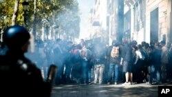 Demonstran berlindung dari gas air mata yang ditembakkan oleh polisi anti huru hara saat demonstrasi rompi kuning, di Paris, Sabtu, 21 September 2019. (Foto: AP/Kamil Zihnioglu)