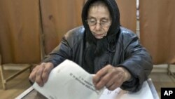 An elderly woman casts a ballot in Sintesti, Romania, Sunday, December 9, 2012.