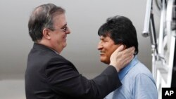 Mexican Foreign Minister Marcelo Ebrard, left, welcomes former Bolivian President Evo Morales upon his arrival to Mexico City, Tuesday, Nov. 12, 2019.