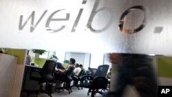 FILE - Employees work at their desks at a Sina Weibo office in Beijing, China, Aug. 1, 2012. Launched in 2009, the Twitter-like microblog site, has been a digital megaphone for millions of Chinese to voice their views on a variety of issues, including a new quiz show critics say is laced with propaganda.