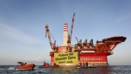 This handout photo taken by Greenpeace on August 25, 2012 shows Greenpeace activists holding a banner in front of the Gazprom 'Prirazlomnaya' oil drilling platform during their protest in the Barents Sea as the Gazprom support boat secures the area.