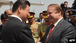 Chinese President Xi Jinping, left, greets Pakistan's Prime Minister Nawaz Sharif at Nur Khan air base in Rawalpindi, in this handout photograph released by Pakistan's press department on April 20, 2015.