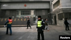 Policemen stand guard in front of a court where Chinese dissident Zhao Changqing's trial is being held in Beijing, Jan. 23, 2014.