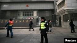 Polisi berjaga di depan sebuah gedung pengadilan di Beijing, tempat berlangsungnya sidang Zhao Changqing (23/1).