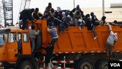 Pekerja migran asal Afrika berupaya naik ke truk setibanya di pelabuhan Misrata dalam operasi evakuasi yang diorganisir IOM.