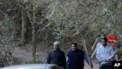 Argentinian judge Martin Perez (L) and experts arrive to Quebrada San Lorenzo natural reserve, 12 km away from Salta, on August 6, 2011. Experts examined again the area after two French women were murdered there last month.