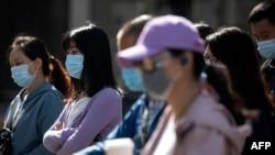Orang-orang yang memakai masker di tengah kekhawatiran virus corona, di sebuah jalan di Beijing pada 13 Mei 2020. (Foto: AFP/Noel Celis)