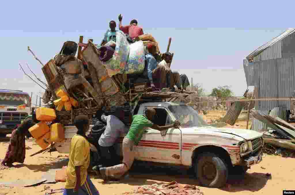 خانوادههای بیخانمان شده در سومالی وانت پر از اسباب و اثاثيهشان را هل میدهند. کمپی که اين خانواده در آن بسر میبرد از طرف ارتش سومالی تعطيل شد و در نتيجه صدها خانوار در موگاديشو بی جا و مکان سرگردانند.