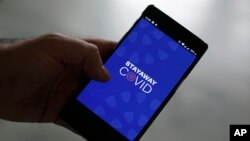 A man shows the contact tracing app Stayaway Covid on his cellphone, in Lisbon, Thursday, Sept. 17, 2020. The smartphone app uses Bluetooth technology to help discover whether people have been in close proximity to someone infected with COVID-19. (AP Phot