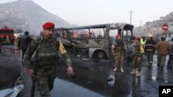 Afghan soldiers stand around a damaged bus at the site of a suicide attack by the Taliban in Kabul, Dec. 13, 2014.