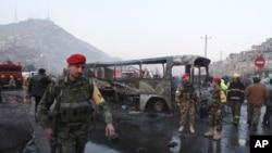 Tentara Afghanistan berjaga-jaga di sekitar bis yang rusak di lokasi ledakan bunuh diri oleh Taliban di Kabul, Afghanistan, Sabtu, 13 Desember 2014.