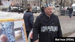 """腐败问题一直困扰俄罗斯。民众更不满腐败猖獗。一名示威者特别穿着印有""""腐败""""的大衣参加今年4月莫斯科市中心的反政府集会。(美国之音白桦拍摄)"""