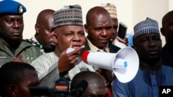Borno state governor, Kashim Shettima (c), addresses demonstrators who were calling on the government to rescue the kidnapped schoolgirls of the Chibok secondary school, in Abuja, Nigeria, May 13, 2014.