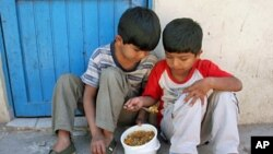 """Two children share food at a Buenos Aires soup kitchen after receiving shoes in TOMS """"Shoe Drop 2006,"""" which donated the company's first 10,000 pairs of shoes in soup kitchens, schools, and to homeless Guarani Indians in the Northern Argentine jungle (200"""