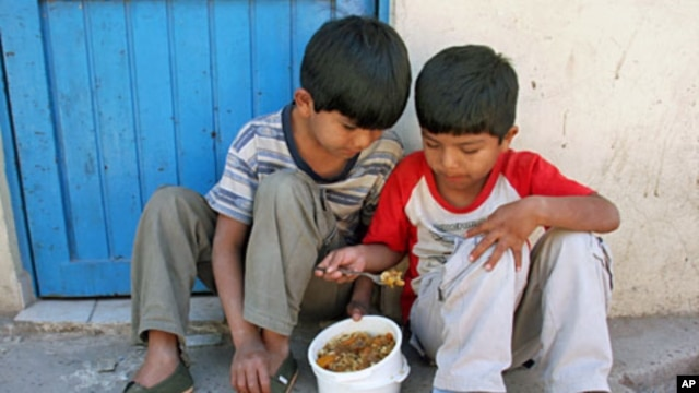 Two children share food at a Buenos Aires soup kitchen after receiving shoes in TOMS