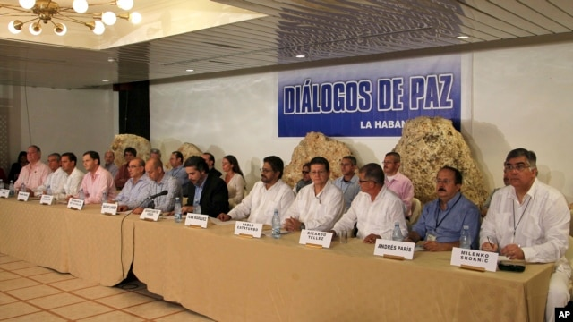 Representatives from Colombia's government negotiation team, left of center, and representatives from the Revolutionary Armed Forces of Colombia, or FARC, negotiation team, right side of table, issue a joint statement in front of a sign that reads in Span