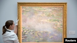 Une assistante de gallerie pose le tableau Nympheas de Claude Monet lors d'une photo-call pour la vente d'art à la maison de ventes Sotheby's à Londres le 18 juin 2014. REUTERS / Neil Hall