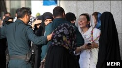 Moral Police (Ghasht e Ershad) tackle a violation of Islamic dress code in Iran in 2014.