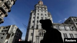 FILE - A man walks in front of the headquarters of Cuba's state-run telecommunications provider ETECSA in Havana.