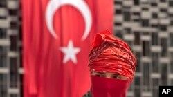ນັກປະທ້ວງຜູ້ນຶ່ງ ເອົາທຸງເທີກີ ມັດຄຸມໃສ່ໜ້າ ຢືນຢູ່ໜ້າທຸງຊາດຂອງເທີກີ ຢູ່ແຄມສວນສາທາລະນະ Gezi Park, ໃນນະຄອນ Istanbul ຂອງເທີກີ ໃນວັນທີ 12 ມິຖຸນາ 2013.