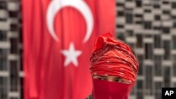 伊斯坦布爾的塔克西姆廣場上一位抗議者站在國旗前面
