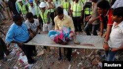 5일 인도 뭄바이에서 발생한 붕괴사고 현장에서 구조대원들이 어린이의 시신을 옮기고 있다.