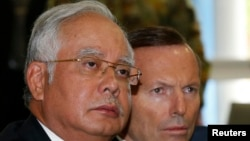 Malaysia's Prime Minister Najib Razak (L) and Australia's Prime Minister Tony Abbott participate in a briefing on the search for Malaysia Airlines flight MH370 at RAAF Base Pearce near Perth, April 3, 2014.