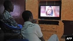 Warga Somalia menonton siaran berita Mogadishu yang menayangkan potret pemimpin al-Shabah yang dikaitkan dengan Al-Qaida, Ahmed Abdi Godane, baru-baru ini dalam seragan udara AS, 6 September 2014.