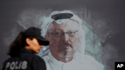 FILE - A Turkish police officer walks past a picture of slain Saudi journalist Jamal Khashoggi prior to a ceremony, near the Saudi Arabia consulate in Istanbul, marking the one-year anniversary of his death, Oct. 2, 2019.