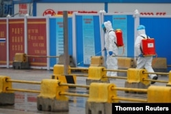 FILE - Workers in PPE spray the ground with desinfectant in Baishazhou market during a visit of World Health Organization (WHO) team tasked with investigating the origins of the coronavirus (COVID-19) pandemic, in Wuhan
