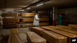 Coffins with the bodies of victims of coronavirus are stored waiting for burial or cremation at the Collserola morgue in Barcelona, Spain, Thursday, April 2, 2020. The new coronavirus causes mild or moderate symptoms for most people, but for some,…