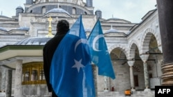 A protester from the Uyghur community living in Turkey stands with flags in the Beyazit mosque during a protest against the visit of China's Foreign Minister to Turkey, in Istanbul on March 25, 2021.
