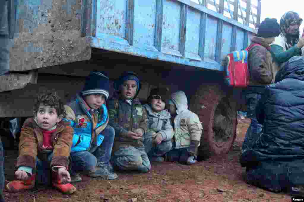 Displaced children, who fled with their families the violence from Islamic State-controlled area of al-Bab, wait as they are stuck in the Syrian village of Akda to cross into Turkey, Jan. 23, 2016. Turkey's border guards prevented the displaced people from approaching their country's border, activists said.