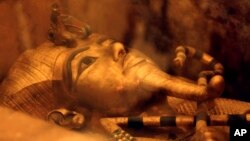 FILE - This April 1, 2016 file photo shows one of Egypt's famed King Tutankhamun's golden sarcophagus displayed at his tomb in a glass case at the Valley of the Kings in Luxor, Egypt