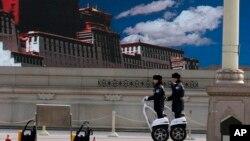 2014年3月9日,警察在天安門廣場巡邏,巨型屏幕上顯示著西藏的藍天白雲。