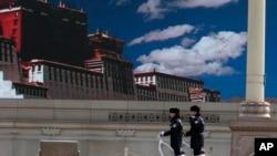 警察在天安门广场巡逻,巨型屏幕上显示着西藏的蓝天白云。(2014年3月9日)