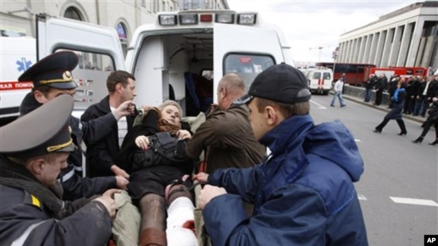 A wounded blast victim is brought by rescuers to an ambulance vehicle in Minsk, Belarus, April 11, 2011