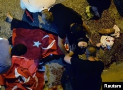 An injured woman draped in a Turkish flag is checked by others near military headquarters in Ankara, Turkey, July 16, 2016.