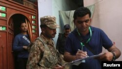 A census enumerator (R) along with a Pakistan Army soldier notes details outside a house