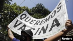 """A man holds a banner reading """"We want vaccine"""" during a protest against new measures implemented to curb the spread of the coronavirus disease in Rio de Janeiro, Brazil, March 26, 2021."""