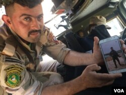 Gunner Ali el-Babli shows a photo of himself after a recent battle, in Mosul, Iraq, May 4, 2017. (H. Murdock/VOA)
