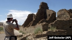 In this photo, tourist Chris Farthing of Suffolks County, England, takes a picture while visiting Chaco Culture National Historical Park in northwestern, New Mexico.