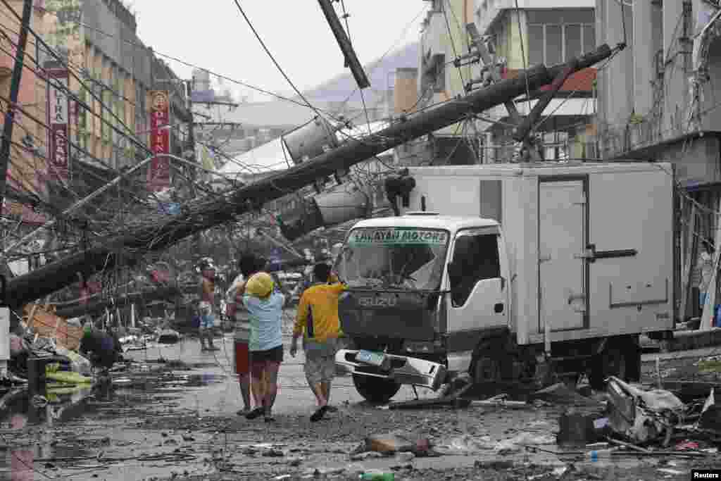 Survivors walk under a fallen electric post after super Typhoon Haiyan battered Tacloban city, central Philippines.