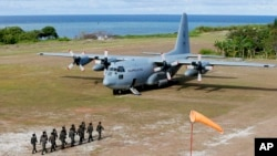 Philippine troops march as a Philippine Air Force C-130 transport plane carrying Defense Secretary Delfin Lorenzana, Armed Forces Chief Gen. Eduardo Ano and other officials, sits on the tarmac at the Philippine-claimed Thitu Island off the disputed Spratlys chain of islands in the South China Sea, April 21, 2017, in western Philippines.