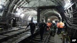 Para petugas mengangkut para korban kecelakaan kereta api bawah tanah di Moskow, Rusia (15/7).